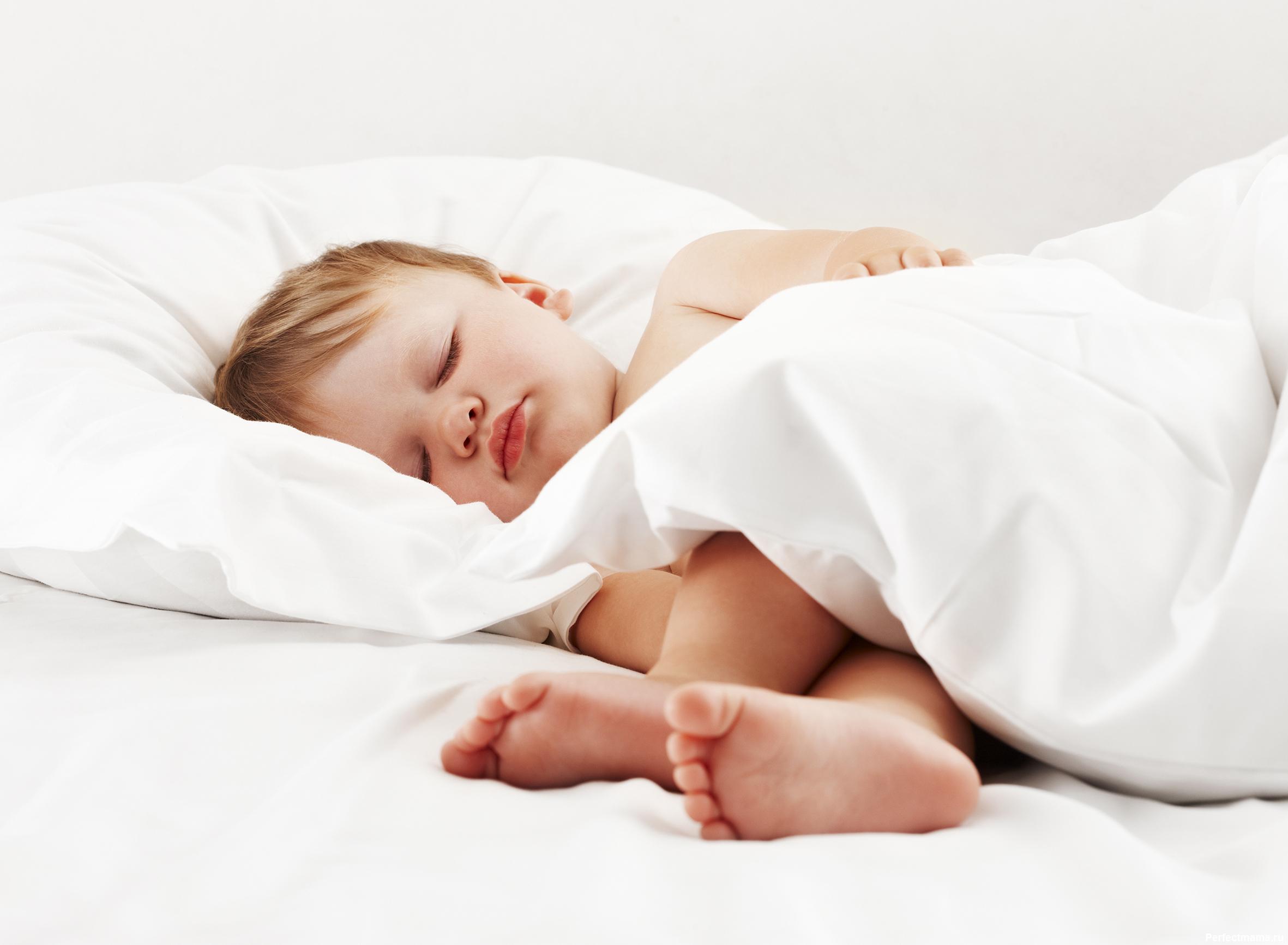 Baby lying on white sheet
